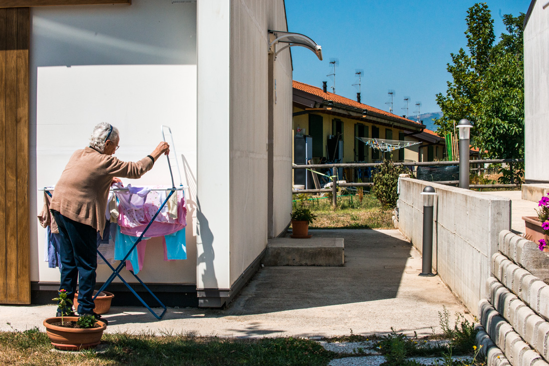 An elderly woman hangs laundry to dry outside the pre-fabricated houses built by volunteers in the months following the earthquake.