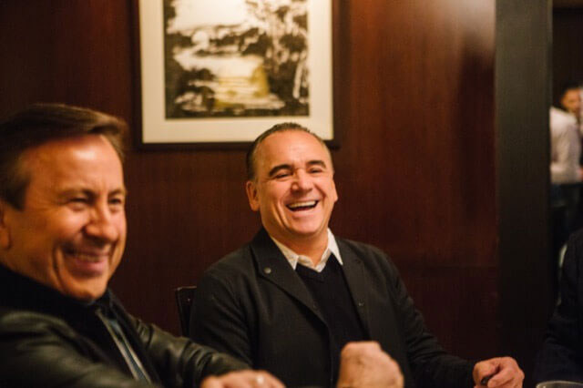 Chef Daniel Boulud and Jean-Georges Vongerichten laugh amid conversation with old friends.