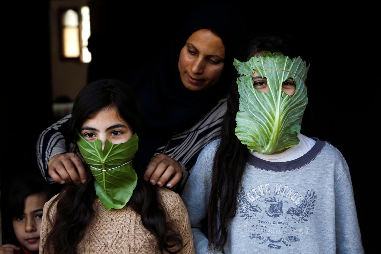 4 дүгээр сарын 16. Газын зурвас дахь Бейт Лахиа хотод хоол хийж байхдаа байцаагаар хийсэн нүүрний хаалтаар хүүхдүүдээ хамгаалж байгаа нь... /Photo by Mohammed Abed/