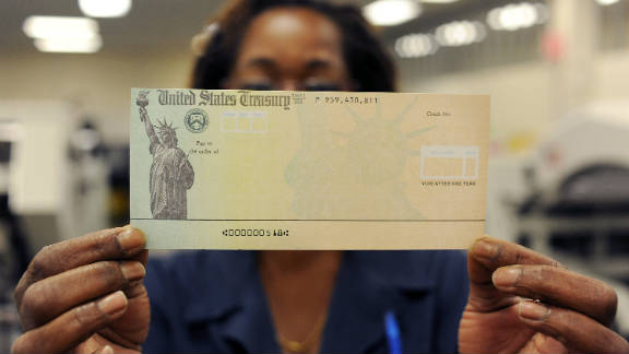 An employee holds a blank check before it