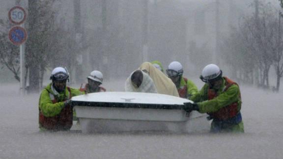 Rescue workers help evacuees through floodwaters in Nagoya.