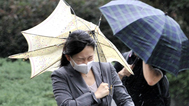 A woman braves strong winds as Typhoon Roke hits the Tokyo area.