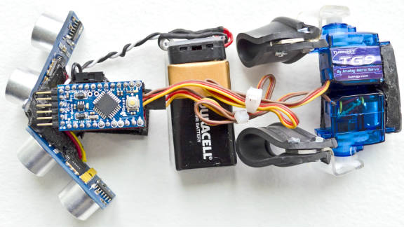 The device has a pair of sensors at the front which send out ultrasonic pulses measuring the distance of objects from one inch to 10 feet. Motorized rubber pads at the rear apply increasing amounts of pressure as users get closer to an object.