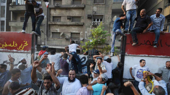 Egyptian demonstrators in 2011 climb on a wall outside the Israeli embassy in Cairo.