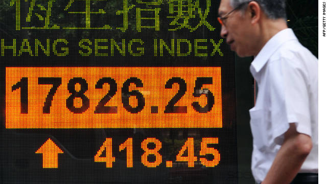 A man walks past a display board showing the Hang Seng stock market index in Hong Kong on September 27.