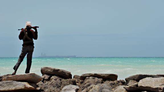 A pirate stands on a rocky outcrop on the coast of Hobyo, central Somalia, 2012