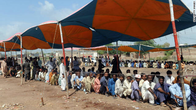 Pakistani flood-affected people queue up at a relief camp in the flood-hit Badin district on September 29, 2011.