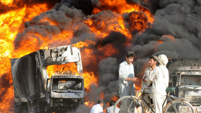 Pakistani residents watch burning NATO supply trucks after another attack on the outskirts of Quetta on September 27, 2011.