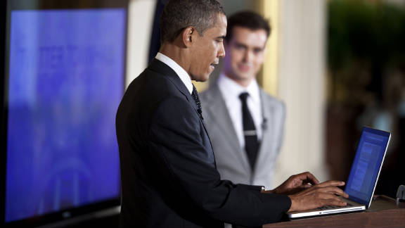 President Obama posts a tweet during an online town hall meeting in July from the White House in Washington.