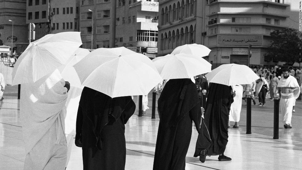 Al Faisal snaps people using umbrellas to protect them from the sun.