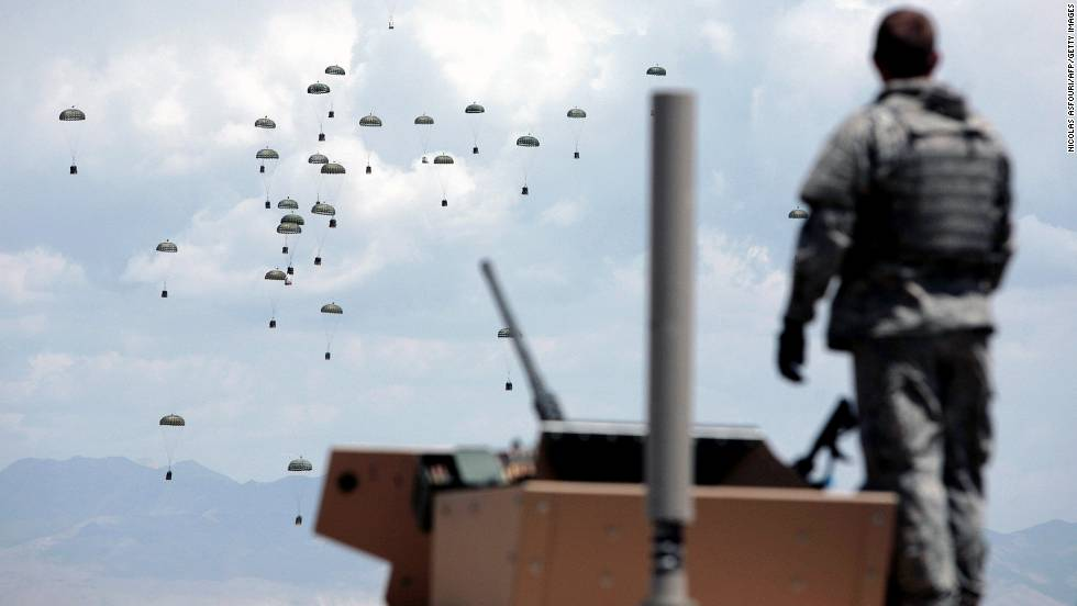 A solider looks on as C-117 plane drops food, water and other supplies onto a landing zone at an undisclosed location in the Ghazni province on May 29, 2007.