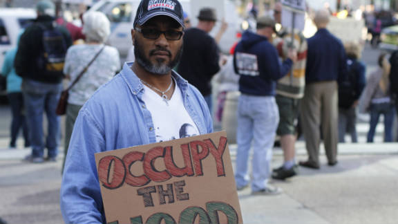 "Jon Perez, 50, is unemployed. ""I wanted to show my support and represent the black and brown community,"" he said. ""How do you level the playing field? You have to challenge the system. I want our voices to be heard, I want to see change in the policies. We're making history. As subtle as it is, there's a movement afoot and this is how it begins."""