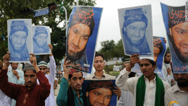 Supporters carry portraits of Mumtaz Hussain Qadri, during a protest against the court verdict in Islamabad.