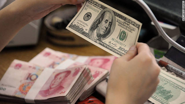 A Chinese bank worker checks a $100 bill together with stacks of 100 yuan notes at a bank in Hefei, east China, on September 30, 2010.