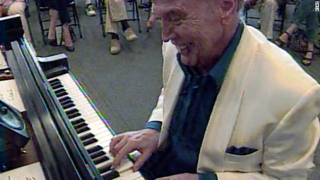 Roger Williams plays on grand piano in Arizona, in 1999, during a 12-hour marathon performance.