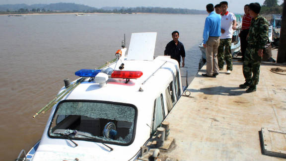 Chinese policemen look at their damaged patrol boat after a gunfight with drug traffickers in Chiang Rai on February 25, 2008.