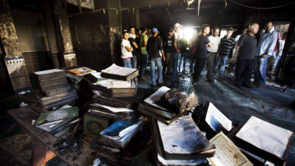 Arab-Israeli men inspect a burnt mosque after it was torched in the Bedouin village of Tuba Zangaria, Israel on October 3.