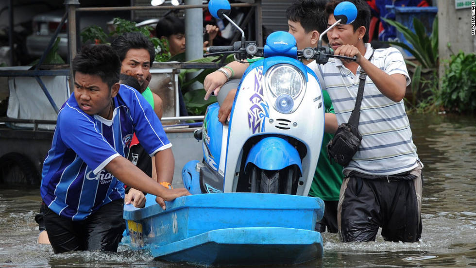 Thai residents transport a scooter over floodwaters along a street in the city of Ayutthaya on October 6, 2011.