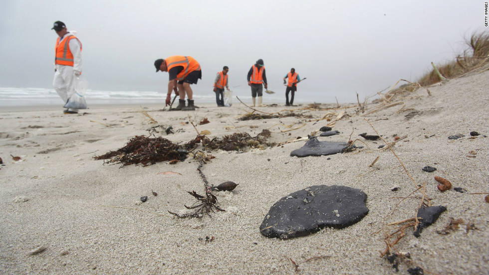Volunteers collect oil clumps washed up on the Mount Maunganui shore on October 11 in Tauranga.