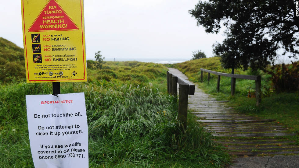 Warning signs are put up on Papamoa Beach on October 12 due to the health hazard posed by the oil spill.