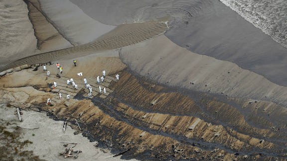 New Zealand soldiers start to clear the oil from Papamoa Beach on October 13 in Tauranga.