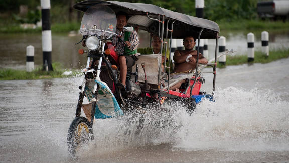 A tuk tuk (taxi) driver tries navigating the flooded streets in Ayutthaya on October 12, 2011.