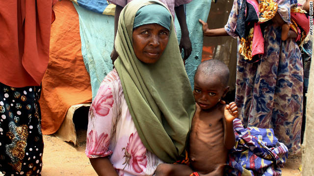 An internally displaced person holds her malnourished child in front of her makeshift shelter on August 25, 2011, at the Taraboonka IDP camp in the Hodon district of Mogadishu.