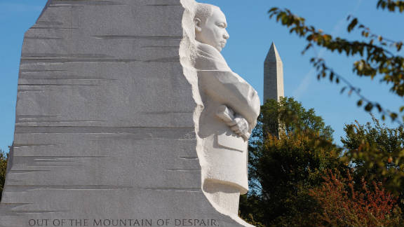 """The memorial site, which features a striking 30-foot statue of King gazing out over the Tidal Basin, lies between the Lincoln Memorial and the Jefferson Memorial on the National Mall. The statue, representing a """"Stone of Hope,"""" sits forward from a """"Mountain of Despair."""""""