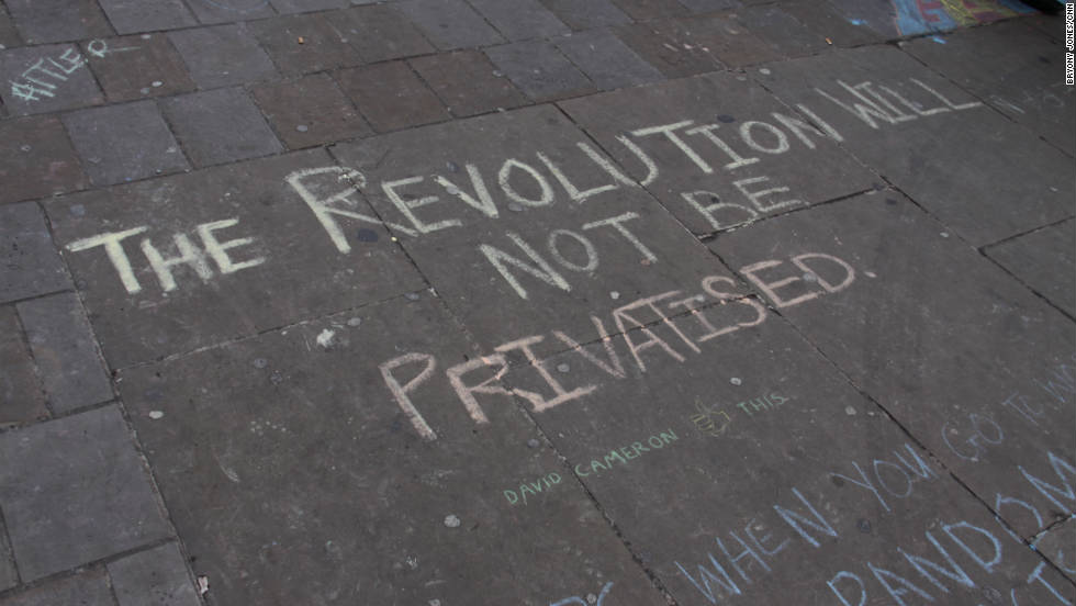 Chalk slogans cover the pavement near the tent village at St Paul's Cathedral.