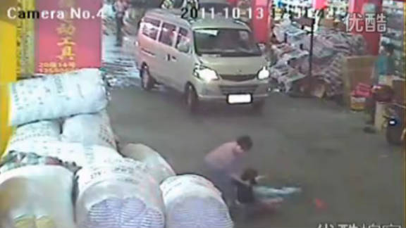 A screen grab of an incident on a China street where a toddler was run down shows a rescuer finally helping her