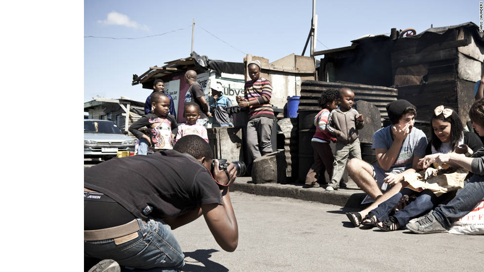 A photographer shoots three of the team in the streets of Langa Township eating a sheep's head. The piece was for the Live Challenge section of the magazine where team members were taken out of their comfort zone to try something new. <br />