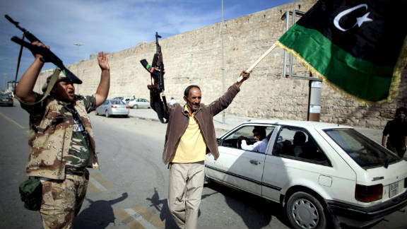 Libyan National Transitional Council fighters celebrate in the streets of Tripoli after news of Moammar Gadhafi