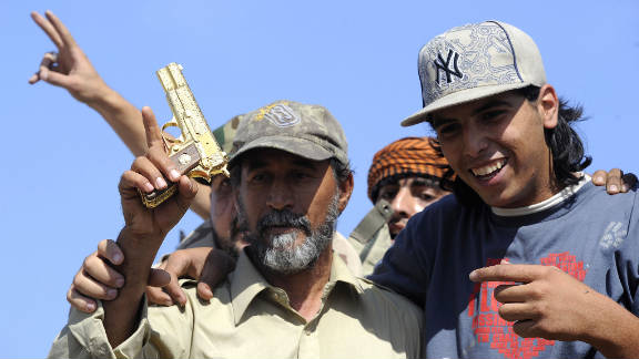 NTC fighters hold what they say is the ousted Libyan leader