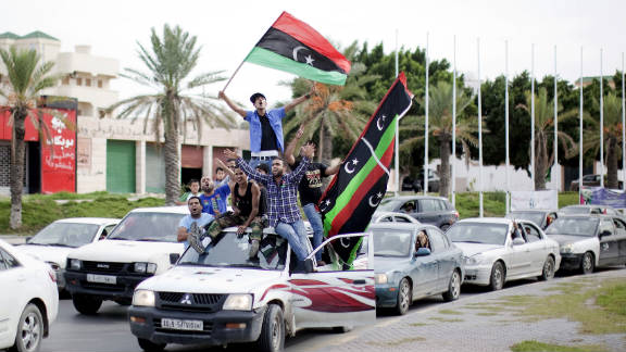 Libyans waving NTC flags celebrate in the streets of Tripoli on Thursday after news of Moammar Gadhafi