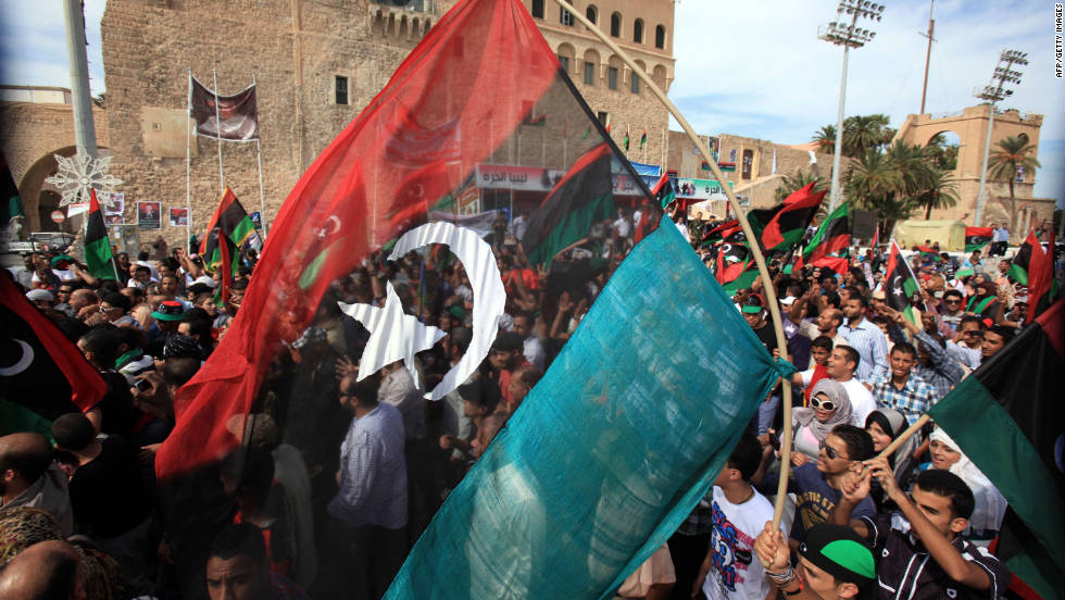 Libyans wave their new national flag as they celebrate in the streets of Tripoli after news of Gadhafi's capture.