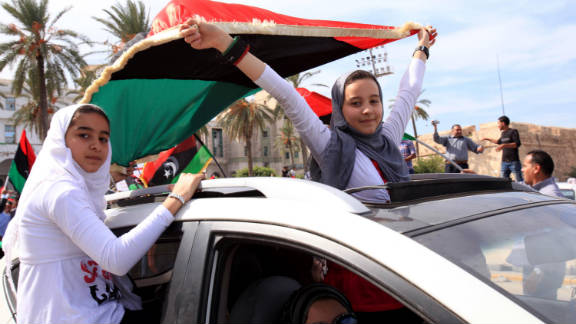 Young Libyan women celebrate with an NTC flag Thursday as they join others in the streets of Tripoli.