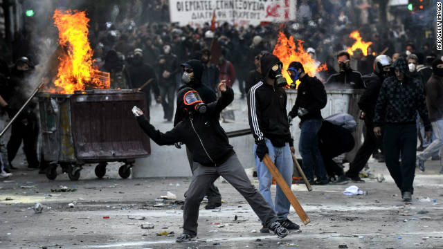 Police clash with masked demonstrators in Athens on October 20,  where tens of thousands of protesters rallied.