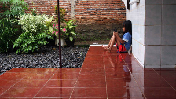 Sim traveled to Indonesia to photograph domestic workers at home with their families. Here a young Indonesian girl sulks hours before her mother is due to leave to work in Singapore.