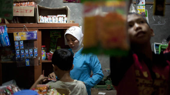 Mutmanah Witono, 38, worked for nine years in Singapore. She returned home to set up a small shop beside her house in Central Java, says Sim.