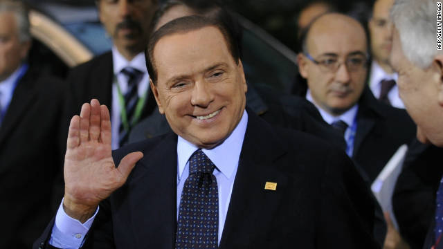 Italian Prime Minister Silvio Berlusconi waves as he arrives prior to a European Council on October 23, 2011.