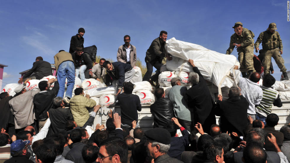 Residents of Ercis collect tents from a Turkish Red Crescent truck on Monday, October 24.