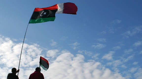 Libyans wave their new national flag and Qatar's flag during a ceremony announcing the liberation in Benghazi on Sunday.