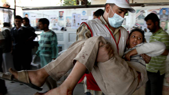 A wounded Yemeni protester is carried by a Red Crescent medic to a makeshift hospital near Sanaa