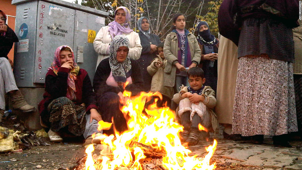 Residents of Ercis gather around a fire to keep warm as they wait in the streets on Tuesday for news of survivors.