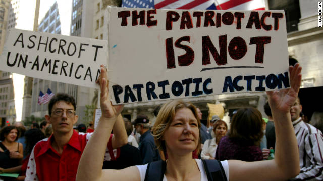 Protesters hold up signs criticizing the Patriot Act and then-U.S. Attorney General John Ashcroft on September 9, 2003 .