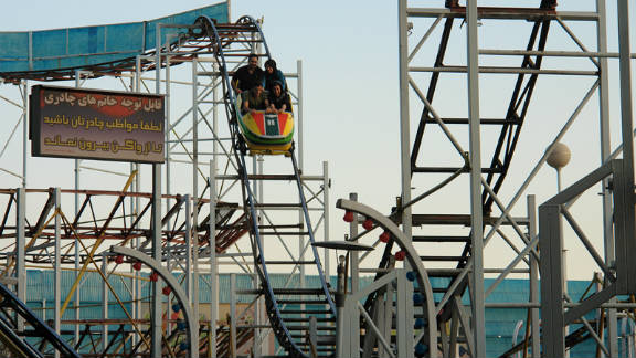 """Riders take the first plunge on one of Eram Park's """"rusting"""" roller coasters."""