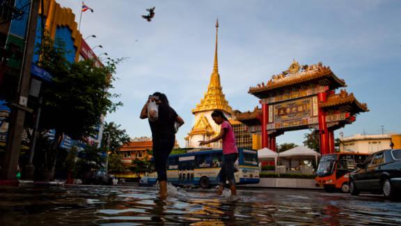 People walk through a flooded street in Bangkok