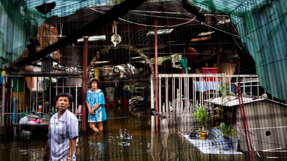 Women stand in a flooded residential area in Bangkok
