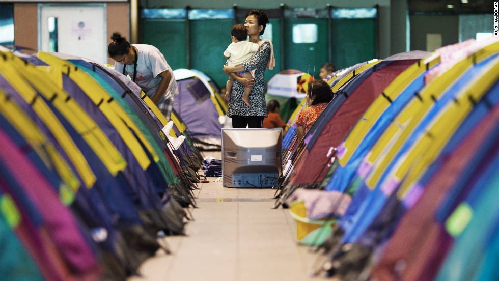 Evacuated residents stand among tents in a shelter set up for flood victims at Don Muang airport. Floodwaters forced the airport to close, and it now serves as a base of flood relief operations.