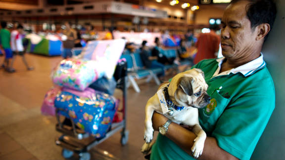A man holds his dog and stands by his belongings at the Don Muang airport. He